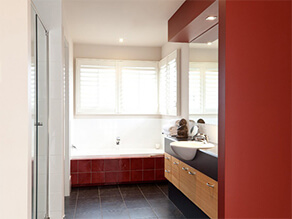 Red Tile Bathroom with Bathtub and Tile Floor and Sink and Black Basin