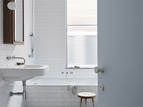 Sleek White Tiled Bathroom with Wooden Framed Mirror and Bathtub Near Window and Blue Door