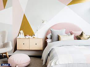 Geometric Gold Feature Wall with Chair and pink cushion with grey carpet and pink and grey pillows