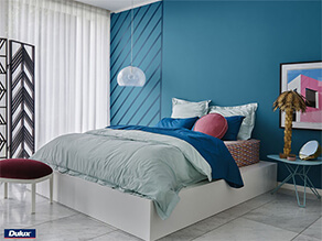 Blue feature wall white ceiling with hanging lamp and artwork and blue pillow with plant tile floor