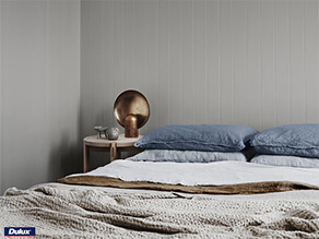 Neutral Grey painted board with textured blankets and blue pillows timber table and rose gold deco