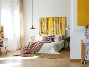 yellow feature artwork on white walls with hanging lights timber floor plants and pink pillows