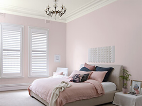 Pink bedroom white ceiling chandelier pink bed cover and pillows with white bedside table and plant