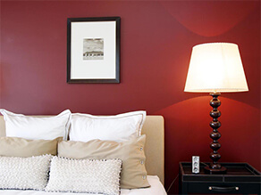 Red Wine Coloured Feature Wall with Cream Coloured Bedsheets