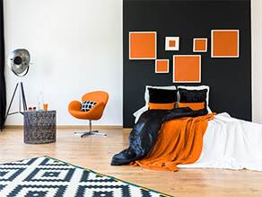 White and black wall with orange feature artwork and deco chair and blankets wooden floor and lamp