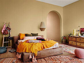 Warm deep tan with boho bed and colourful rugs orange pillow and wooden floor
