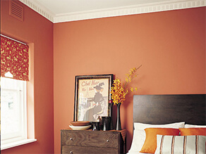 Orange bedroom with white ceiling and dark wooden furniture white bedding orange pillows