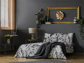 Dark grey feature wall bedroom with wooden floor and gold artwork plants and white bedding pillows