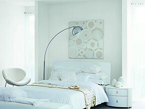 Clean White Bedroom with White Bed Covers and Pillows with Chair and bedside table and lamp
