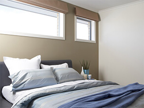 Khaki feature wall bedroom white ceiling with blue bed covers and pillows with plant and vase