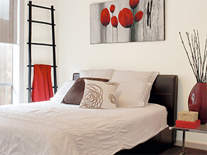 Neutral bedroom with pops of red colour in artwork, towels and decorations, ladder plant and pillows