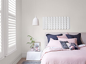 White walls bedroom with pink bedding and pillows with beside table and hanging light and plant