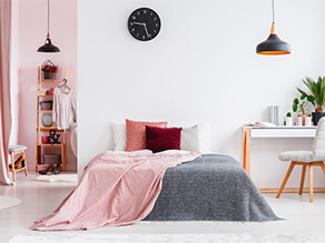 Modern bedroom with white and pink walls, pink and grey throw rugs and study desk with black clock