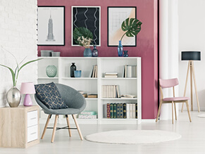 Pink feature wall with bookshelf and chair and wooden table with plants and lamps with exposed brick