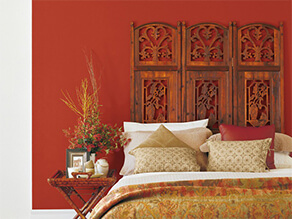 Red oriental bedroom with wooden bedhead and bamboo bedside table with gold throw blanket and pillow