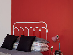Bright red feature wall in kids bedroom with white and black pillows and lamp with grey bed sheets