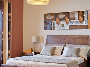Neutral bedroom with brown artwork and dark wooden bedhead and brown wall and cream bedding pillows