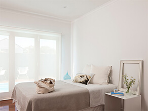 Neutral modern simplistic bedroom with beige bed covers white pillows with plant on bedside table