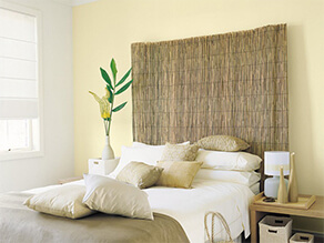 Light yellow feature wall with bamboo bedhead and plant on bedside table with gold pillows