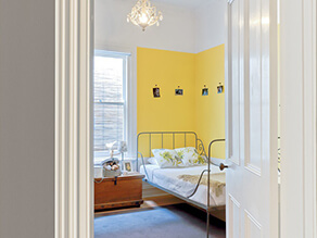 Yellow feature wall corner in bedroom with white bedding and wooden side table with photos carpet
