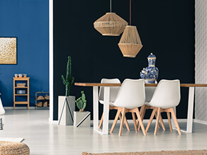 Dark Bold dining setting with pop of blue paired with light white and wooden furniture and plants