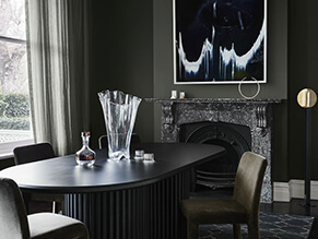 Dark green moody dining room setting with fireplace and dark table and chairs with curtains