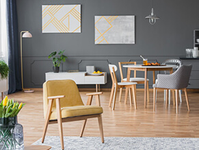 Grey modern dining setting with yellow chair timber floor and table with plants grey chair