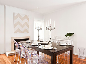 White Modern Dining Room with Timber Floorboards and clear chairs and dark wooden table and candles