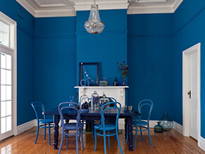 Bold blue feature dining room with white trims and doors and blue table and chairs and ornaments