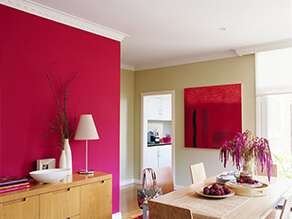 Bright pink feature wall in dining room with wooden table and red artwork plants and drawers