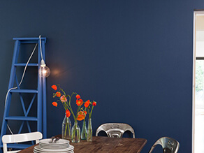 Industrial chic blue feature wall with dark timber table and metal chairs with ladder and flowers