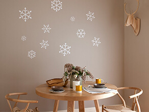 Soft neutral dining setting with painted snowflakes and timber table and chairs and deer head art