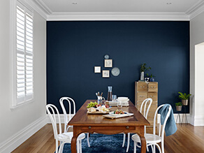Dark navy blue feature wall white walls contrast with timber floor boards and table white chairs