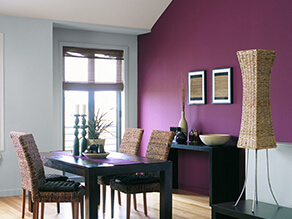 Pink feature wall with contrasting blue grey wall dark brown table and desk with cane chair