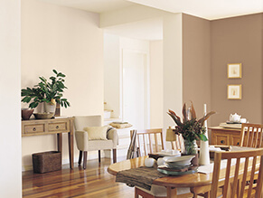 Neutral brown traditional dining setting with wooden floorboards and dining table and chairs plant