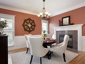 Orange feature room with bronze chandelier and fireplace with white chairs and dark wooden table