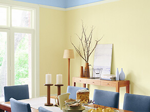 Colourful yellow and blue dining room with timber table and bench with plush blue chairs and candle