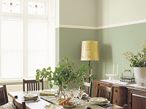 Traditional dining setting with a pop of green on the walls yellow lamp plants and wooden table