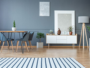 Modern grey dining room with nautical rug and wooden floor plants white bench lamp
