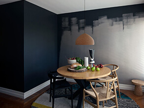 Deep moody dining room with grunge paint timber table and floor with rug and hanging lamp