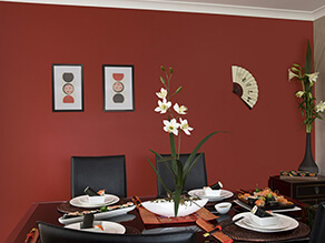 Red oriental dining room with black table and chairs white plates and plant with fan art