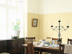 Traditional yellow dining room timber dining table with candle and dark wooden drawes with plant