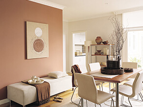 Neutral dining space with timber table and cream chairs and brown blanket on cushion bench plant