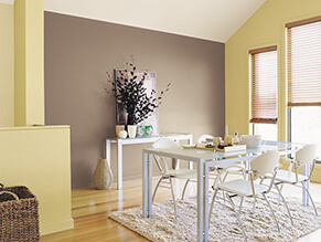 Fresh bright lemon dining room with neutral wall and clean white table and chairs with cosy rug
