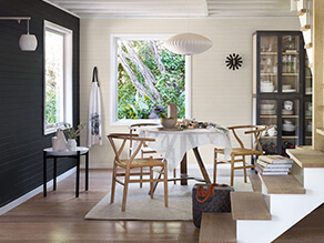 Modern charcoal dining room with wishbone chairs and cream contrasting walls with rug on floorboards