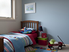 Baby_blue_feature_wall_childs_bedroom_cream_widow_sills_blue_red_green_striped_blankets_pillows