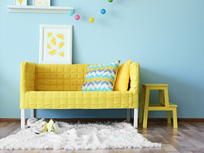 Bright_Kids_Room_Blue_Wall_timber_floorboards_yellow_plush_couch_stool_fluffy_white_rug_artwork