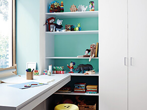 Childrens_study_area_blue_painted_feature_wall_white_hidden_shelf_dinosaur_toys_desk_yellow_stool