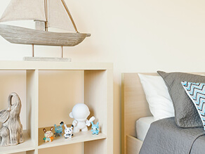 Neutral_kids_bedroom_toddler_minimalistic_timber_cube_shelving_timber_boat_ornament_grey_blanket
