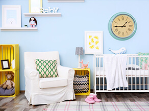Pale_Blue_Nursery_Painted_Yellow_crates_white_covered_seat_green_pattern_pillow_slippers_rug